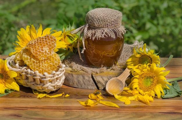 Vasetto di miele fresco, mestolo di legno e favi nel campo dei fiori di campo. miele in campo di fiori selvatici