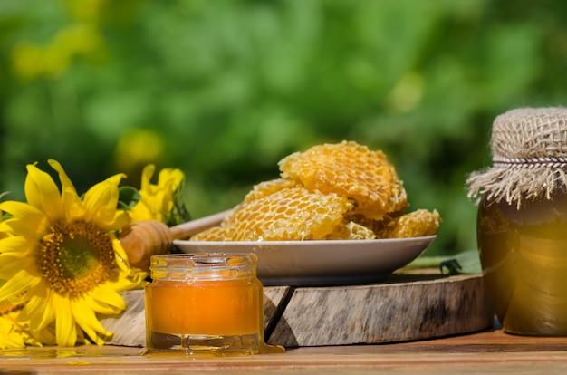Vasetto di miele, mestolo, vaso di miele fresco, nido d'ape su un tavolo di legno all'aperto
