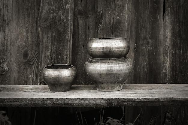 Vasi antichi per la cottura nella retro annata di stile rustico del fondo di legno scuro russo del forno