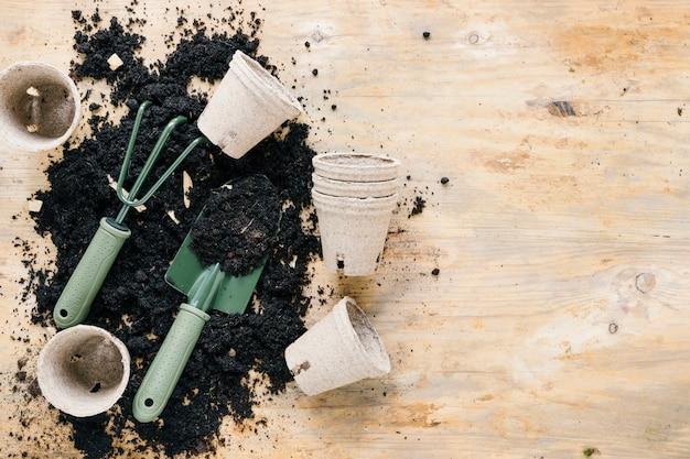 Vasi di torba e attrezzi da giardinaggio con terreno nero su tavola di legno
