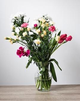 Vaso alto angolo con fiori che sbocciano