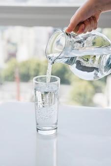 Vaso che riempie un bicchiere d'acqua