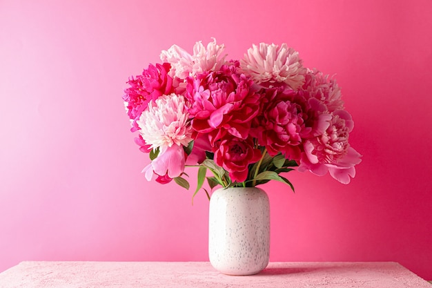 Vaso con bouquet di belle peonie sul tavolo rosa su sfondo di colore