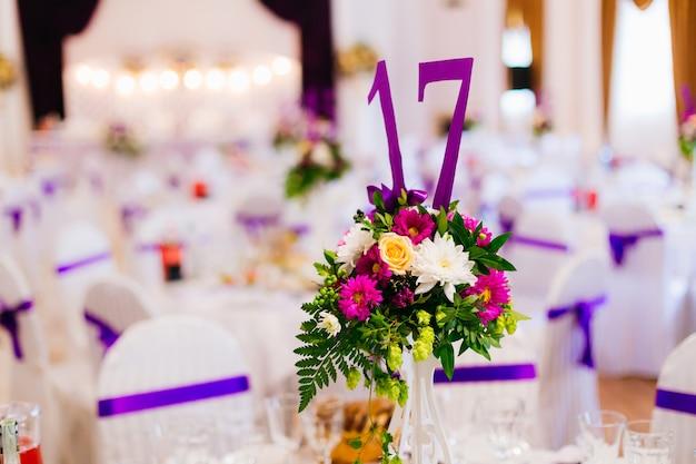 Vaso con fiori e numero sul ricevimento di nozze