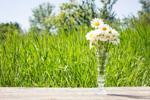 Vaso con margherite su un vecchio tavolo di legno