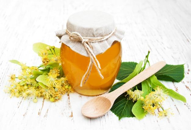 Vaso con miele e fiori di tiglio su un tavolo