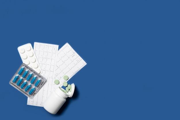 Vaso con pillole e compresse in blister. cardiogramma, malattie cardiache. sfondo blu, posto per il testo.