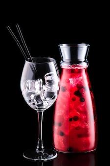 Vaso con sangria con frutti di bosco e un bicchiere di vino isolato su sfondo nero