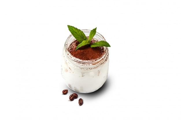 Vaso con tiramisù. dessert delizioso di mascarpone del cioccolato con i biscotti inzuppati in caffè. cosparso di cacao e cannella con un rametto di menta. alimento isolato su un bianco