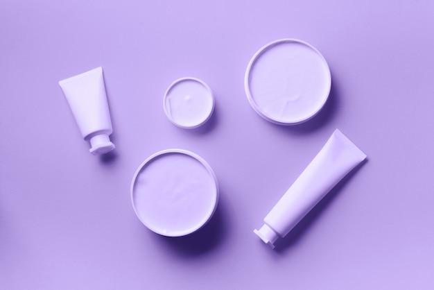 Vaso cosmetico bianco, tubo, bottiglia e foglia di monstera tropicale