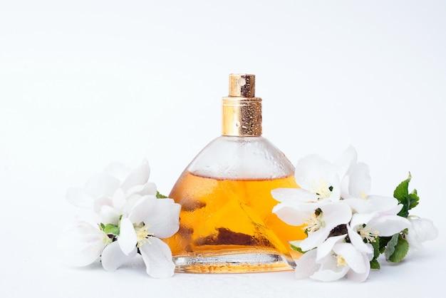 Vaso d'oro di profumi femminili su sfondo bianco con fiori sbiaditi primaverili e gocce d'acqua