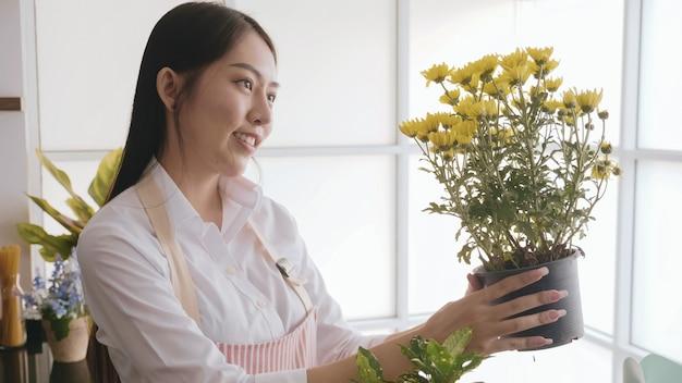 Vaso da fiori felice della tenuta della donna del giardiniere dei fiori nella stanza.