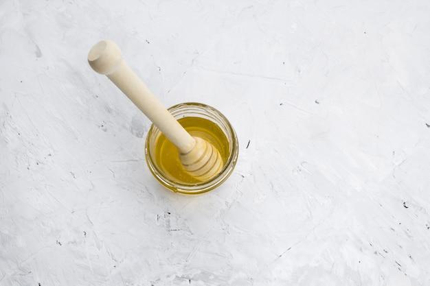Vaso del miele di vista superiore con il cucchiaio di legno su un fondo misero concreto bianco