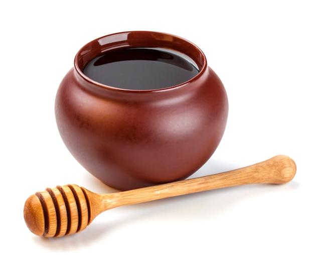 Vaso del miele e bastone del miele isolati su bianco