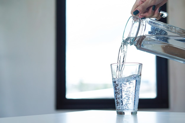 Vaso della holding della mano della donna di acqua e acqua di versamento in un vetro