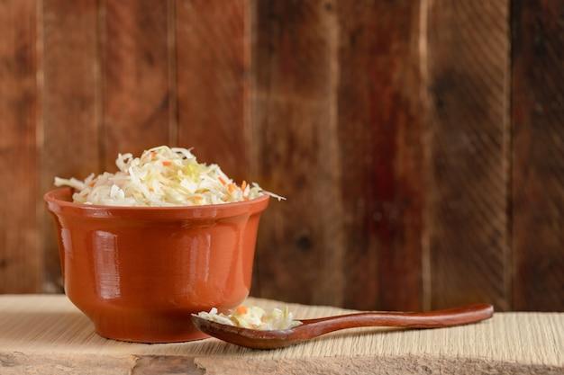 Vaso di argilla marrone e cucchiaio di legno con crauti
