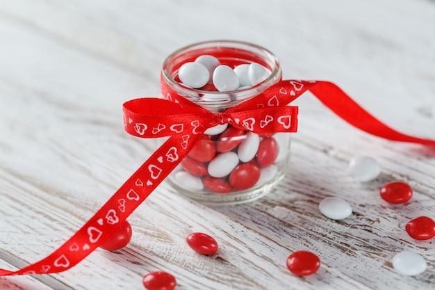 Vaso di caramelle colorate decorato con cuori di un fiocco rosso. concetto di san valentino
