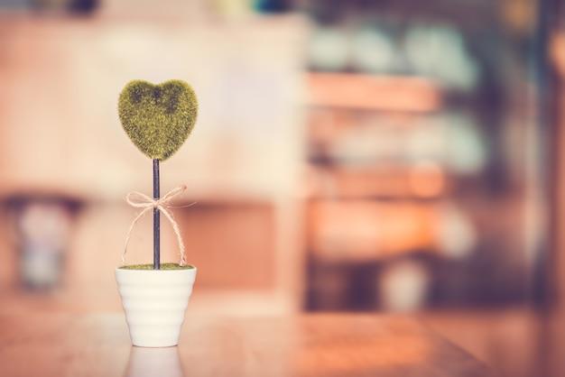 Vaso di fiore con cuore verde sulla tavola di legno con lo spazio della copia e del bokeh