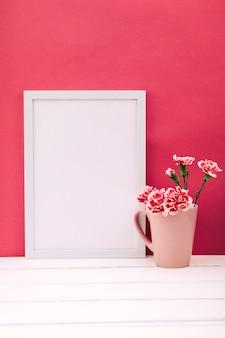 Vaso di fiori di garofano con cornice vuota sulla tavola di legno bianco