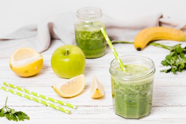 Vaso di frullato sano con fette di mela e limone