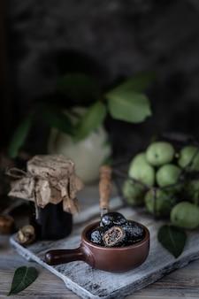 Vaso di marmellata di noci su un tavolo di legno e un gruppo di noci verdi.