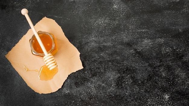 Vaso di miele con cucchiaio e vista dall'alto