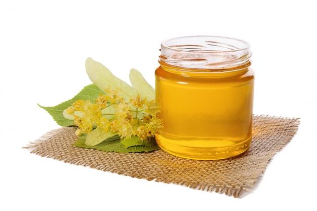 Vaso di miele di tiglio e tiglio fiorito su bianco