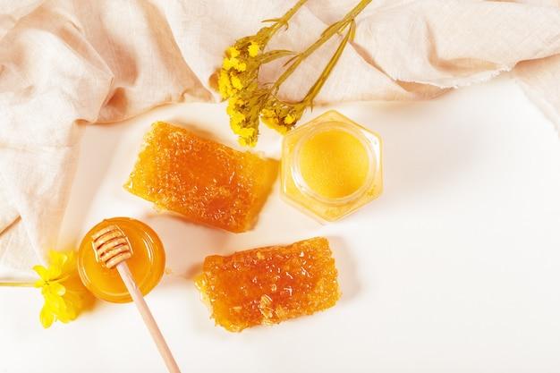 Vaso di miele e bastone isolato su bianco