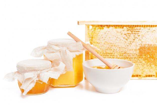 Vaso di miele e bastone isolato su sfondo bianco