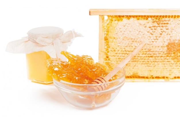 Vaso di miele e bastone isolato
