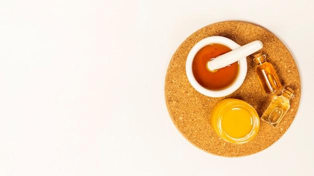 Vaso di miele e olio essenziale su sughero marrone su sfondo bianco