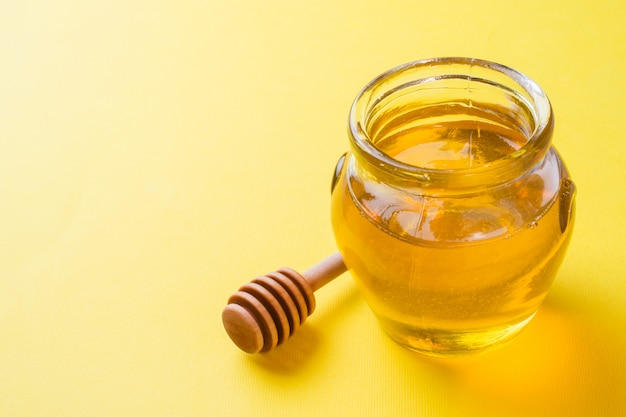 Vaso di miele liquido e un bastone sulla superficie gialla. copia spazio.