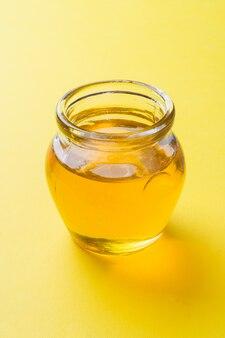 Vaso di miele liquido su superficie gialla. verticale