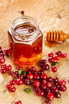 Vaso di miele mestolo alto angolo e frutti rossi