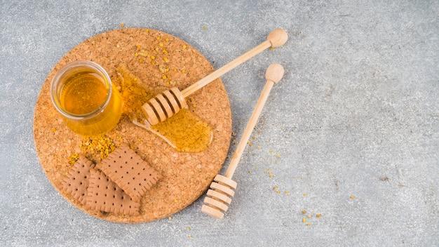 Vaso di miele; polline d'api; biscotti e merluzzo miele sul sottobicchiere sullo sfondo concreto