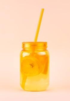 Vaso di muratore arancione di limonata con limoni e ghiaccio e paglia su un corallo molle.