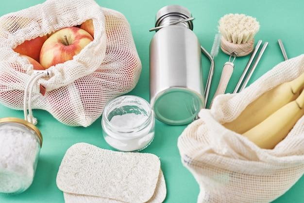 Vaso di vetro, cannucce di metallo, bottiglia di alluminio, spazzola per la pulizia in legno e frutta nel sacchetto della spesa, vista dall'alto