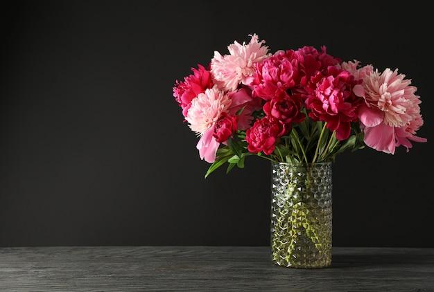 Vaso di vetro con bouquet di belle peonie sul tavolo di legno su sfondo nero