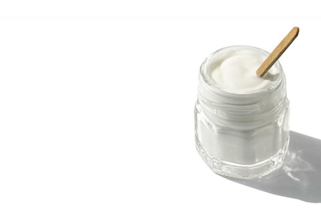 Vaso di vetro con crema e bastone di legno