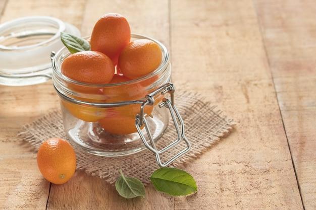 Vaso di vetro con gustosi frutti di kumquat sul tavolo di legno, spazio per il testo