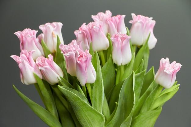 Vaso di vetro con i tulipani rosa su una tavola di legno scura, su un fondo accogliente o su un concetto
