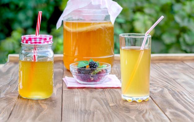 Vaso di vetro con kombucha, un bicchiere versato con kombucha e una tazza con la mora in un giardino estivo.
