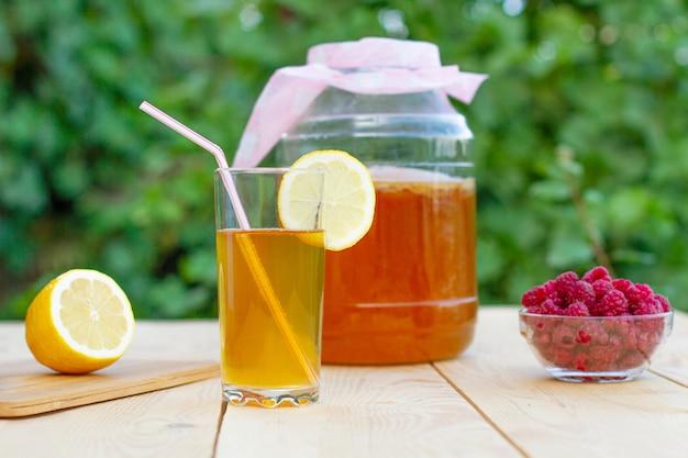 Vaso di vetro con kombucha, vetro versato con kombucha e lamponi nel giardino estivo.