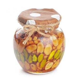 Vaso di vetro con miele dolce isolato