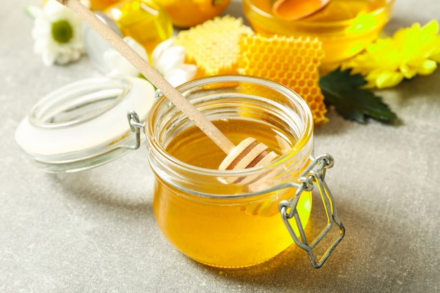 Vaso di vetro con miele, mestolo, favi e fiori su grigio