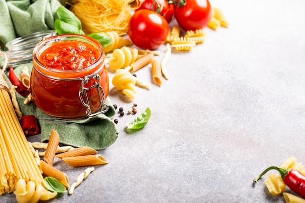Vaso di vetro con pasta di pomodoro piccante classica fatta in casa o salsa di pizza.