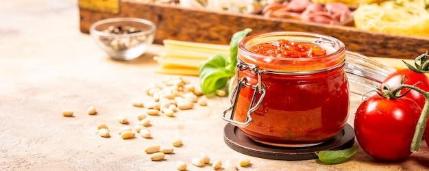 Vaso di vetro con pasta di pomodoro piccante classica fatta in casa o salsa per pizza.
