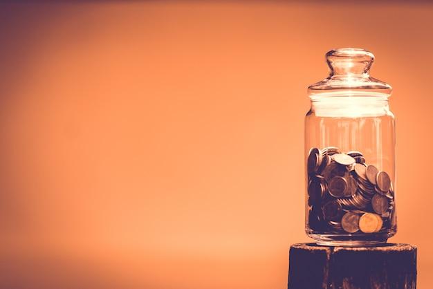 Vaso di vetro con soldi su legno con sfondo arancione e uno spazio vuoto per l'immissione di testo.