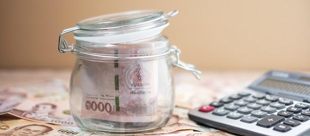 Vaso di vetro di denaro con calcolatrice. affari, investimenti, finanza