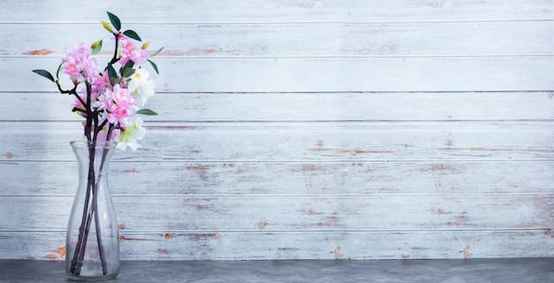 Vaso di vetro di fiori di ciliegio essiccati su legno texture di sfondo a parete, copia spazio.